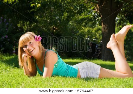 Young Smiling Girl Lies On The Grass