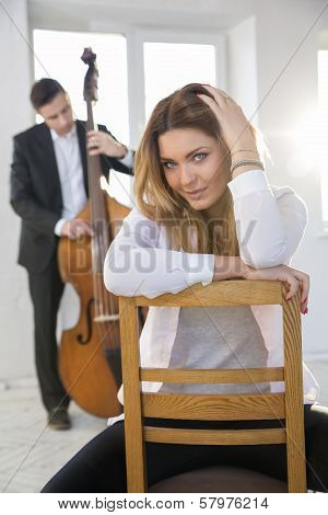 Woman On Chair And Man With Contrabass