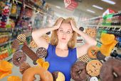 stock photo of starving  - A woman has sweet food snacks around her on in a grocery store - JPG