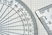 foto of protractor  - plastic protractor with triangle over graph paper - JPG