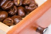 stock photo of wooden box from coffee mill  - Grains of black roasted coffee in drawer of mill - JPG