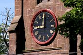 stock photo of brownstone  - Large red clock on an old nineteenth century brownstone church tower reading nine a - JPG