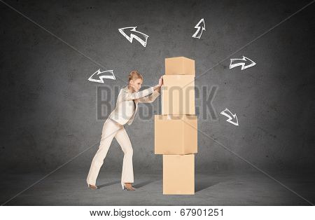 business, postal and office concept - businesswoman pushing tower of cardboard boxes with direction arrows