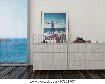 Room overlooking the sea with wooden chests of drawers decorated with ornaments and artwork, a wooden parquet floor and large view window overlooking the blue ocean