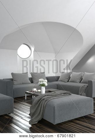 Modern grey living room interior with a circular window set in a sloping alcove above an upholstered grey lounge suite and wooden parquet flooring