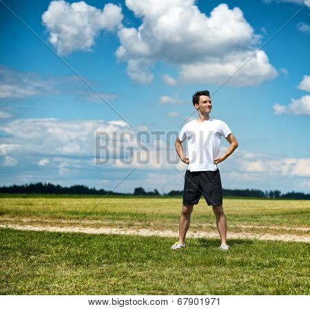 Fit proud determined young male athlete standing with his hands on his hips in open countryside alongside a rural track as her savors the warmth of the sunshine while taking a break during training