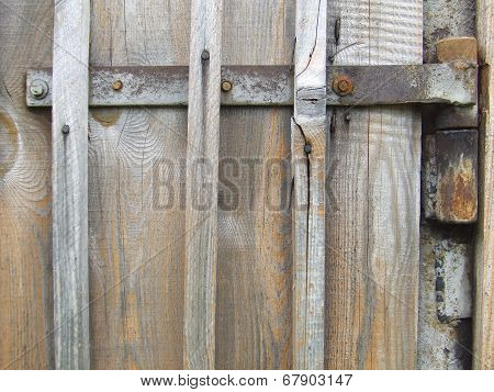 Rusty hinges on the old wooden gate from boards