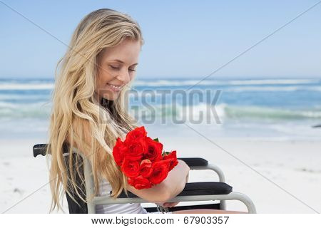 Wheelchair bound blonde smiling on the beach holding roses on a sunny day