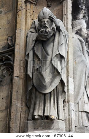 PARIS, FRANCE - NOV 11, 2012: Saint Denis statue, Church of St-Germain-l'Auxerrois founded in the 7th century, was rebuilt many times over several centuries.