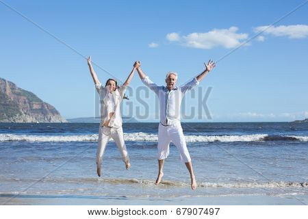 Happy couple jumping up barefoot on the beach on a sunny day