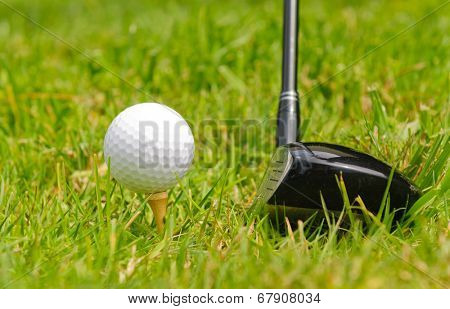 Golf ball on a tee with #3 wood set for a left handed golfer,