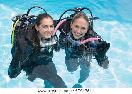 Smiling friends on scuba training in swimming pool making ok sign on a sunny day