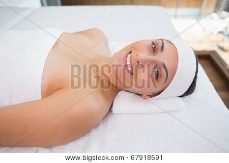 Peaceful smiing brunette lying on massage table in the health spa