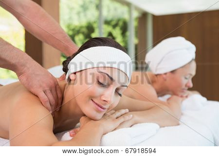 Pretty friends getting massages together in the health spa