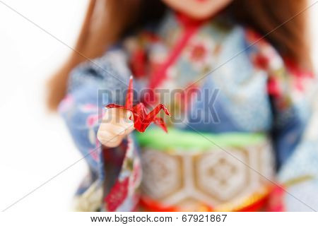 A Miniature Origami Bird And A Japanese Doll In Kimono