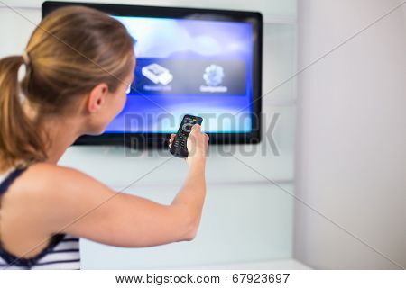 Young woman at home watching TV, turning it on, changing channels
