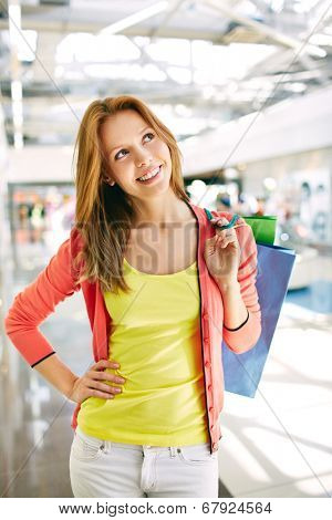 Portrait of happy girl with shopping bags in the mall