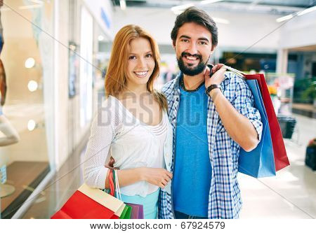 Portrait of young couple with paperbags looking at camera in the mall
