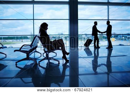 Outline of businesswoman sitting in airport on background of her colleagues handshaking by the window