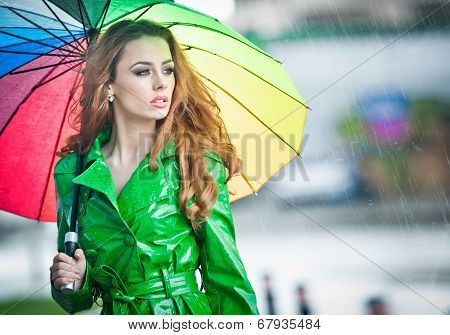 Beautiful woman in bright green coat posing in the rain holding a multicolored umbrella. Dramatic