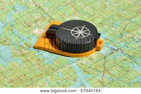Compass Lies On A Topographic Map.