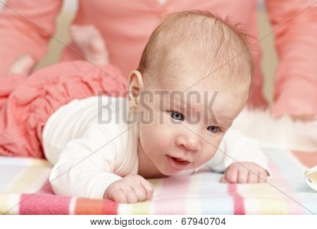Closeup photo of tiny newborn baby lifting head.