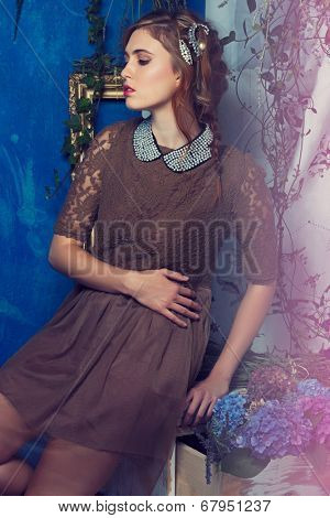 portrait of a beautiful woman with red hair in curly braided hairstyle. wearing a romantic lace dress with pearl collar on grunge blue background