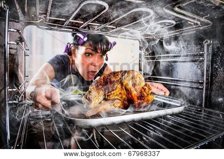Funny Housewife overlooked roast chicken in the oven, so she had scorched (focus on chicken), view from the inside of the oven. Housewife perplexed and angry. Loser is destiny!