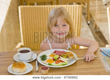 Young girl eating in restaurant