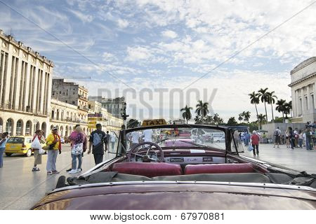 HAVANA, CUBA - DEC 30, 2009: Old vintage american car commonly used as taxi parked in crowded Havana street.