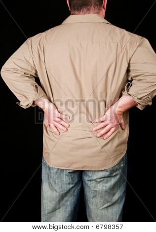 Male With Back Pain On Black Background