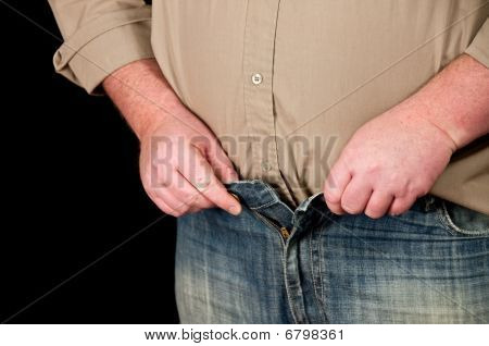 Male In Jeans Open Waistline On Black Background