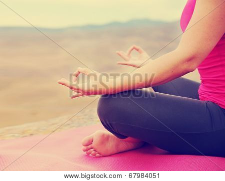 a woman meditating in a yoga pose on a hill top rock done with a soft retro vintage instagram