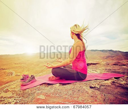 a woman meditating in a yoga pose on a hill top rock done with a soft instagram like glowing filter