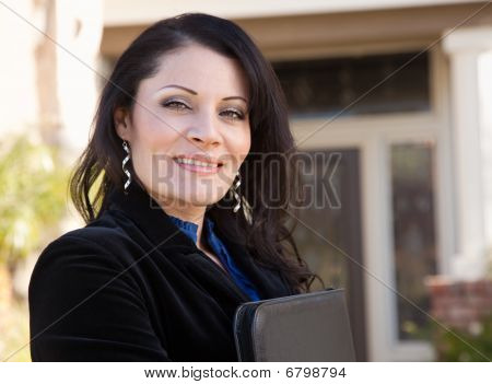 Attractive Hispanic Female Business Woman In Front Of New Home