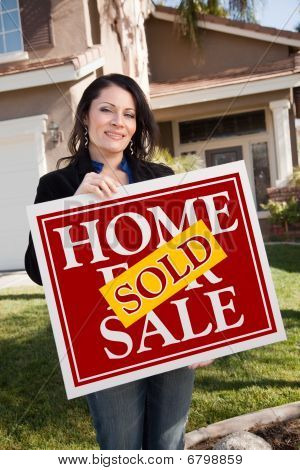 Hispanic Woman Holding Red Sold Real Estate Sign In Front Of House