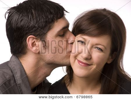 Man kissing woman on the cheek.