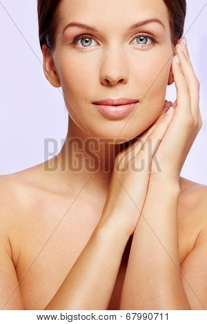 Gorgeous woman touching her face and looking at camera