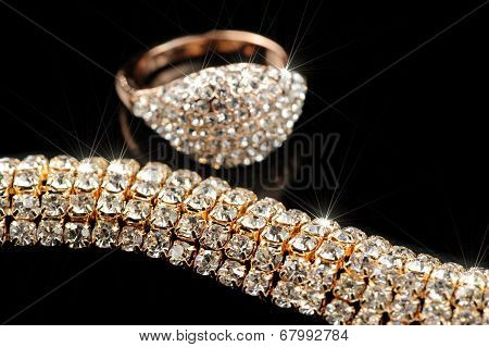 Shiny Gold Ring And Necklace On Black Background