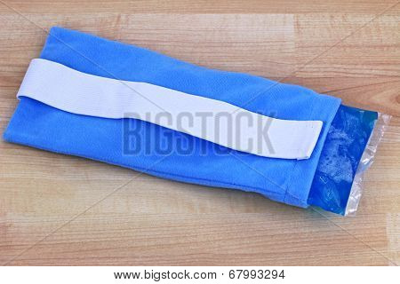 A blue reusable soft gel-filled cold and hot pack to relieve pain inside a fabric pouch