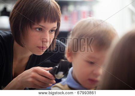 Hairstylist cutting a young boys hair