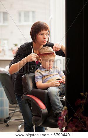 Little boy getting a haircut from hairdresser