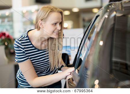 Woman admiring a car at an auto show