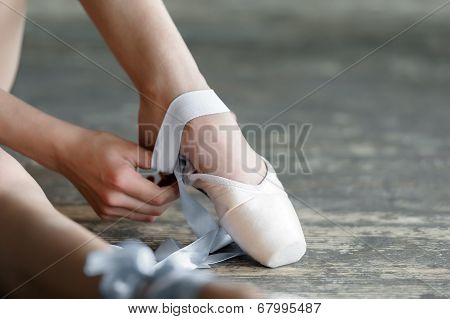 Taking off the ballet shoes after rehearsal or performance