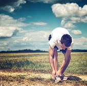 foto of bend over  - Sportsman on a rural track in open countryside bending over tying his laces on his running shoes before commencing his workout and training - JPG