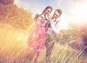 stock photo of lederhosen  - Loving couple in traditional Bavarian Dirndl and Lederhosen eat a brezel outside - JPG