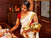 picture of panchakarma  - Woman having ayurvedic massage with pouch of rice - JPG