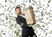 stock photo of heavy bag  - young businessman holding heavy paper bag with money under dollar - JPG
