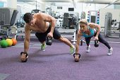 stock photo of kettlebell  - Bodybuilding man and woman lifting kettlebells in plank position at the gym - JPG
