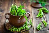 stock photo of pea  - Fresh green peas on a wooden table - JPG